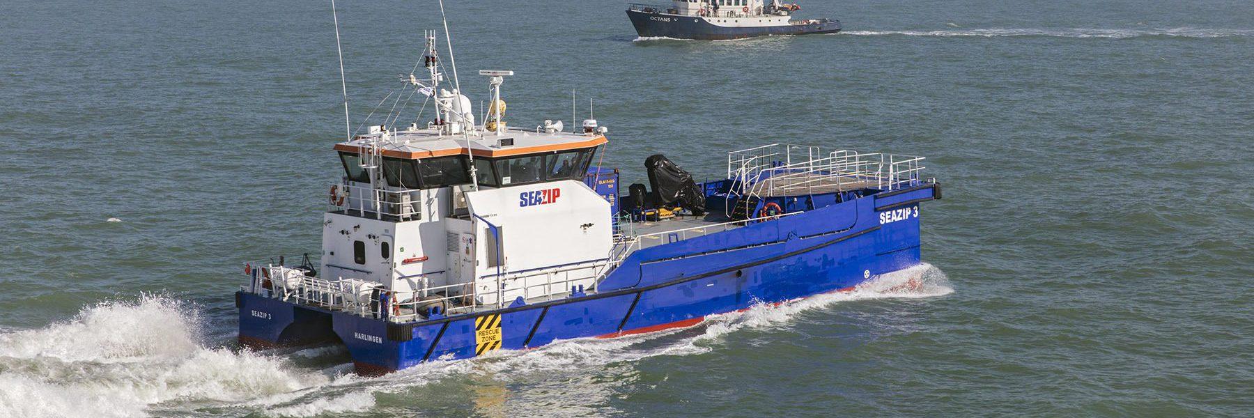 Een schip van SeaZip dat autonoom vaart over de zee. Het schip is blauw aan de onderkant en wit aan de bovenzijde.