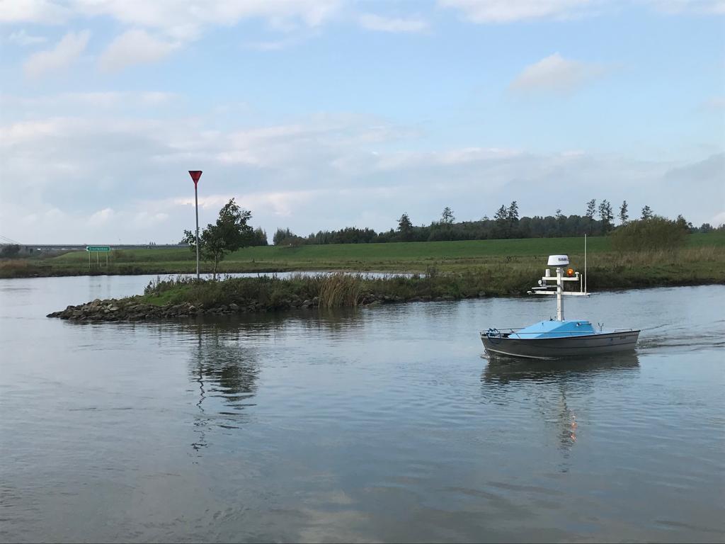 Een kleine drone vaart op het water naast een groene krib