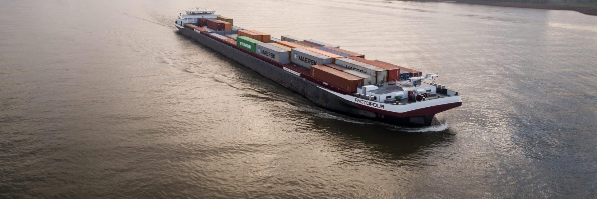 Een vrachtschip op het water. Op de achtergrond is een grote brug te zien.